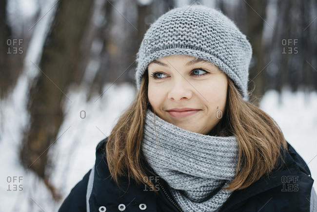Portrait of smiling young woman wearing scarf and hat in winter park