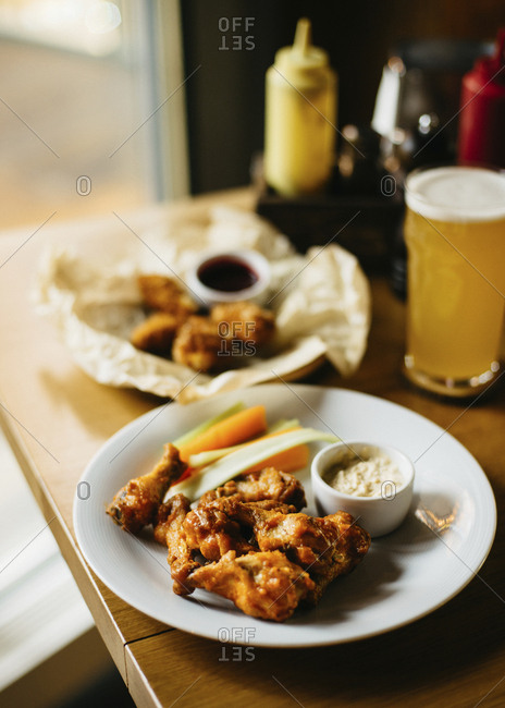 Spicy hot chicken wings with blue cheese sauce and glass of beer
