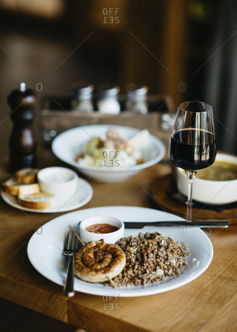 Lunch at restaurant with glass of wine, grilled sausage and buckwheat