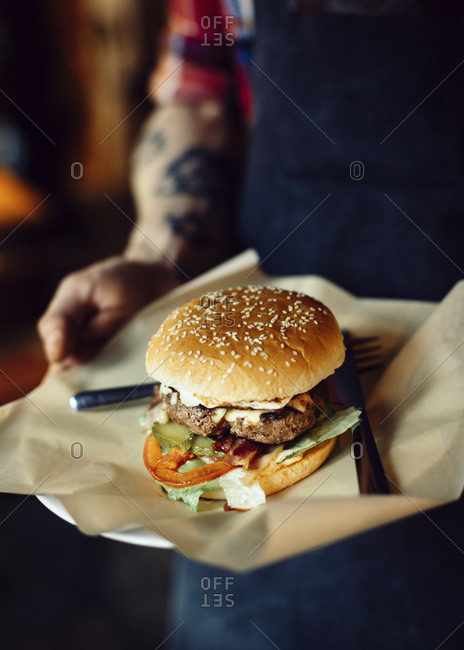 Waiter holding big fresh burger with juicy beef cutlet