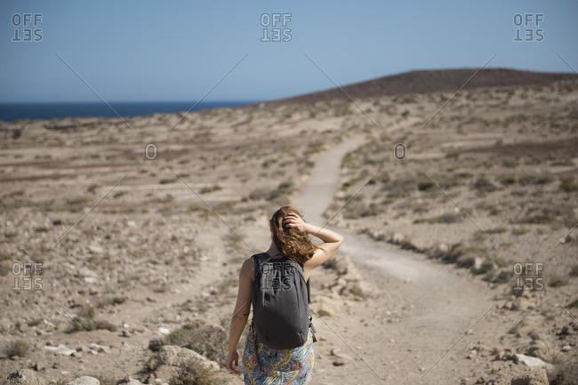 Female traveler with backpack walking through desert area against sky