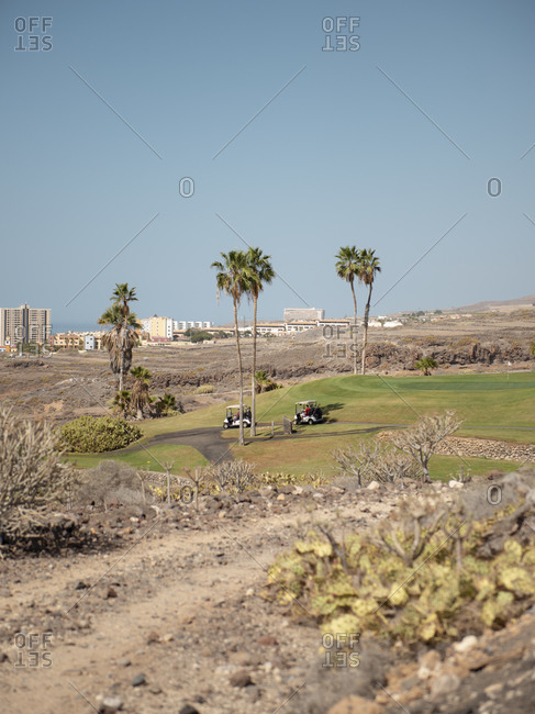 Two golf carts on the path of a golf course during sunny day