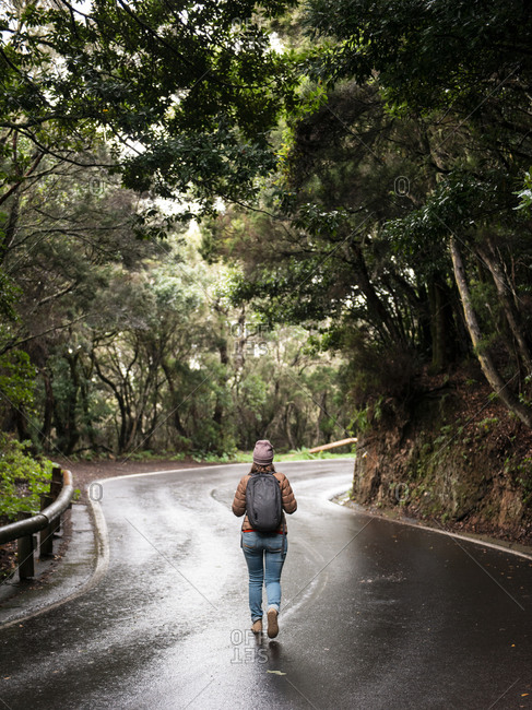 Rear view of girl walking on empty road passing through green forest