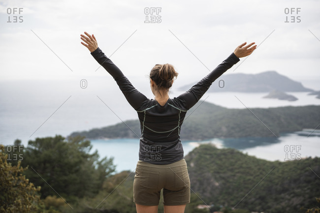 Rear view of carefree woman with arms outstretched against seascape