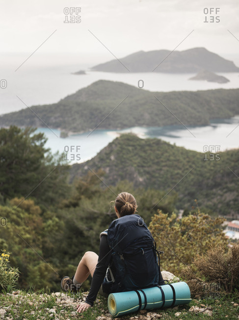 Rear view of female hiker sitting on the hill and looking at seascape