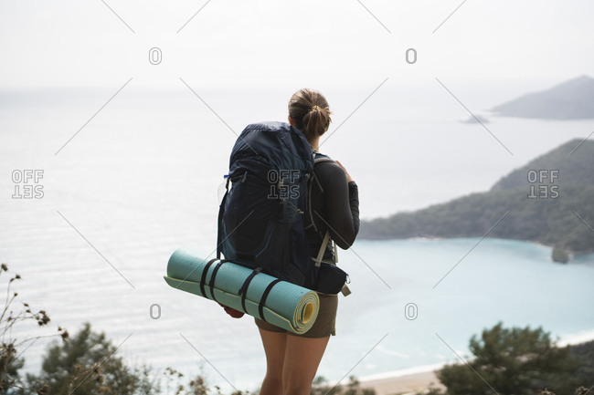 Rear view of female hiker looking at seascape from the top of mountain