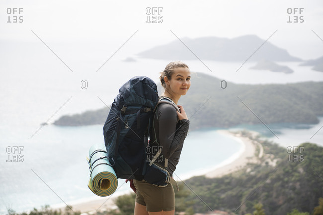 Woman with backpack standing against seascape and looking at camera