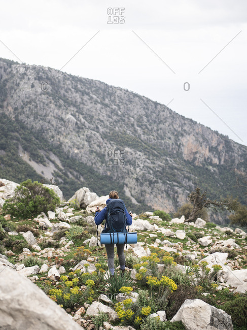 Rear view of female hiker walking by rocks to the top of the mountain
