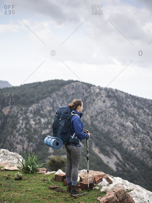 Woman with backpack standing and enjoying view from top of mountain