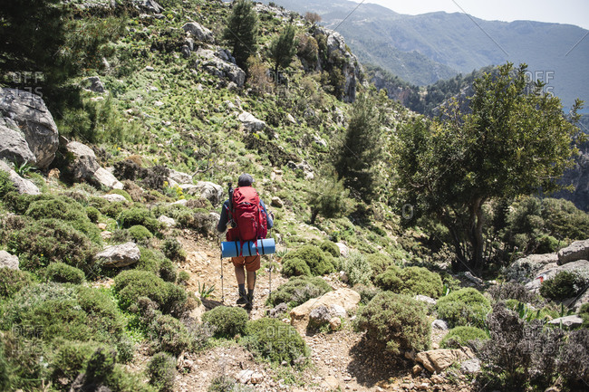 Rear view of man with backpack going down rocky mountains by sunny day