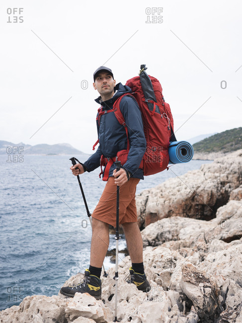 Man with backpack standing on the rocky seacoast and looking away
