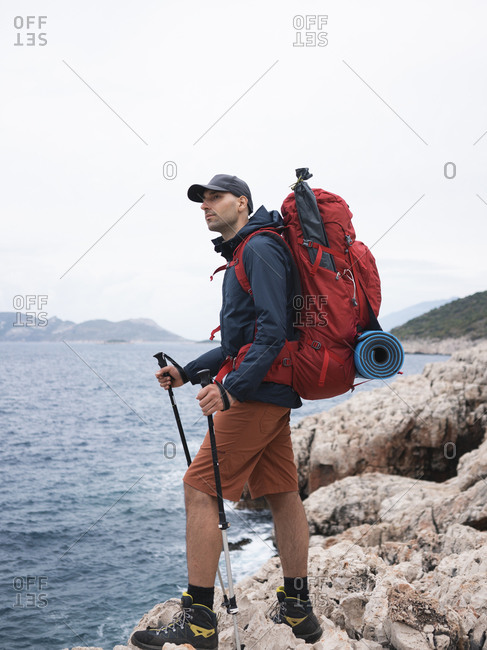 Man with backpack standing on the rocky seacoast and looking at sea