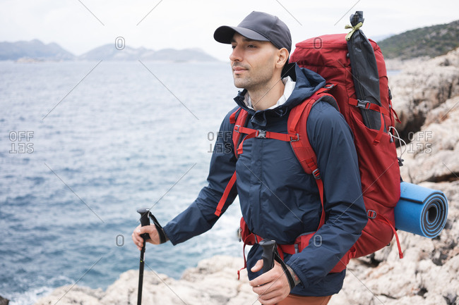Man with backpack standing on the rocky coast and looking at seascape