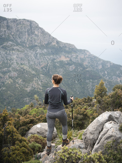 Rear view of woman enjoying the view from a high mountain viewpoint