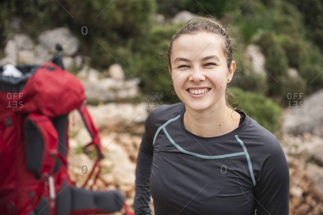 Portrait of happy smiling female hiker looking at camera outdoors