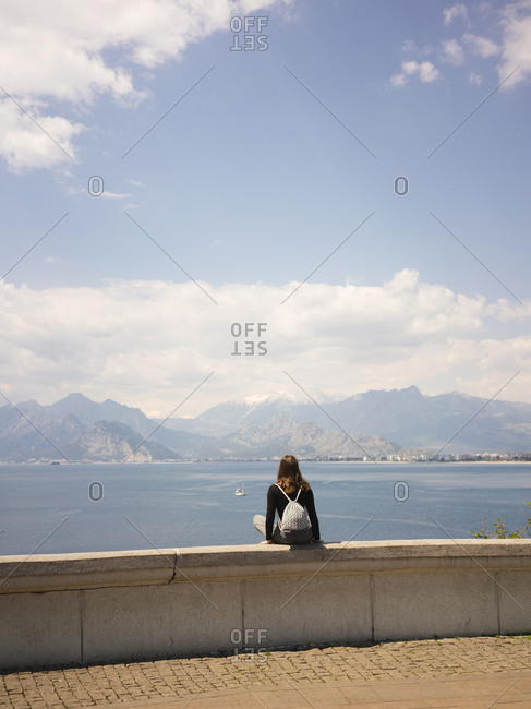 Rear view of young woman sitting on seaside and looking at seascape