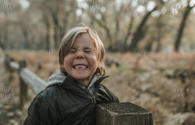 Playful boy with eyes closed clenching teeth by wooden fence at Yosemite National Park