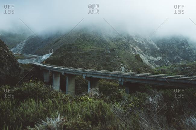 Bridge amidst mountain during foggy weather