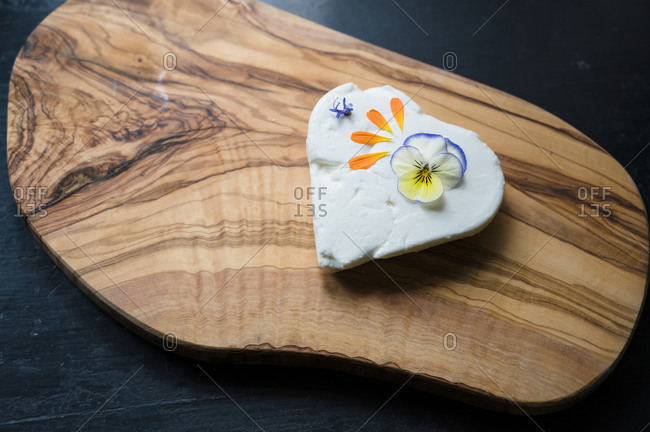 Overhead view of heart shaped goat cheese with edible flowers