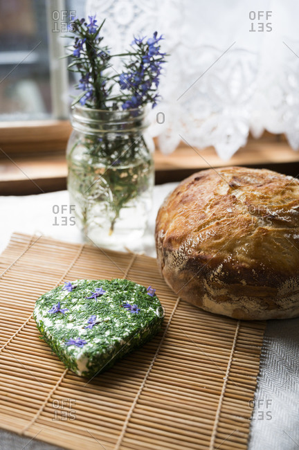 Herb goat cheese with loaf of fresh bread and jar of rosemary