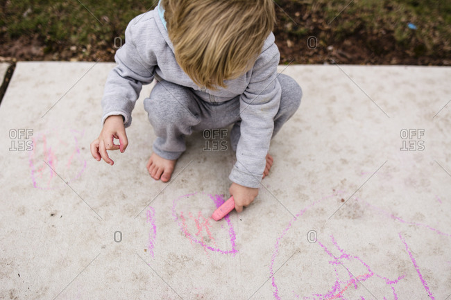High angle view of boy drawing on footpath with chalk