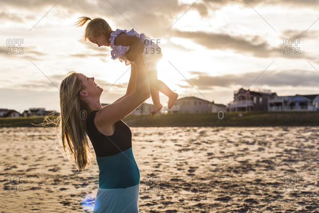 Side view of playful mother lifting daughter while playing by lake against cloudy sky