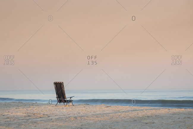 Empty chair at Florida beach against clear sky during sunset
