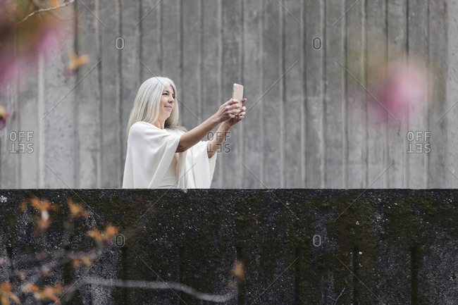 Woman taking selfie while standing by retaining wall