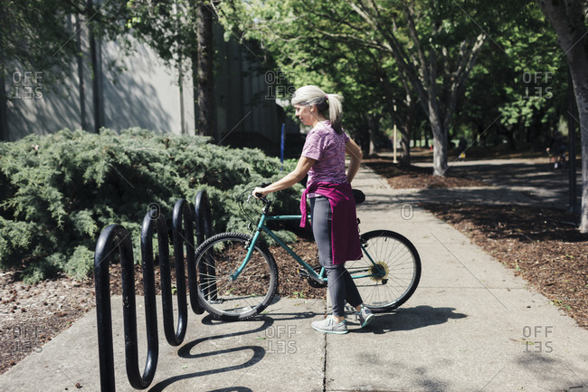 Side view of woman with bicycle standing on footpath at park