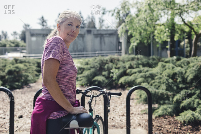 Portrait of woman with bicycle standing on footpath at park