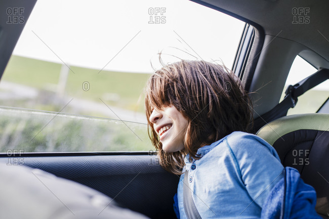 Smiling kid on the back looking away through the window in car