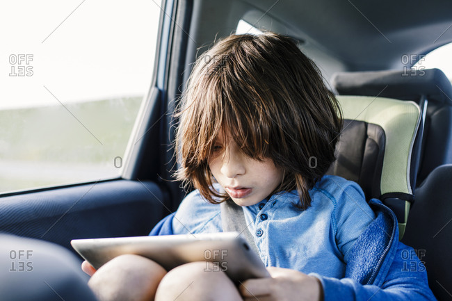 Child using a tablet while in car seat