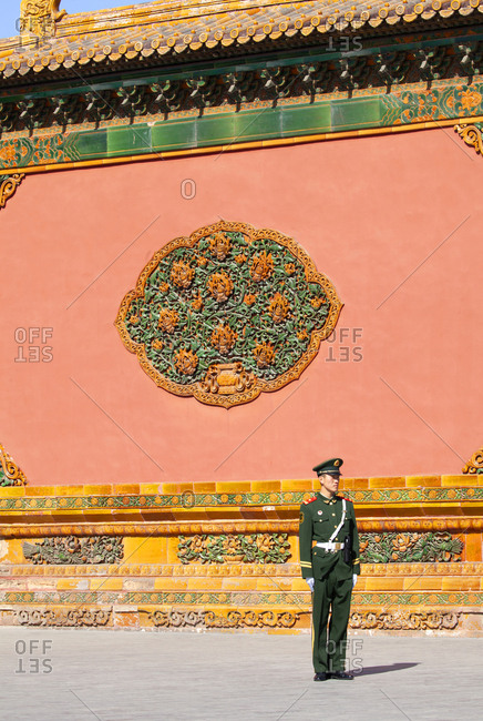 Beijing, China - March 22, 2016: Guard standing by ornate wall of The Forbidden City