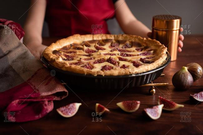 Close-up of girl holding home-baked fig tart dark background