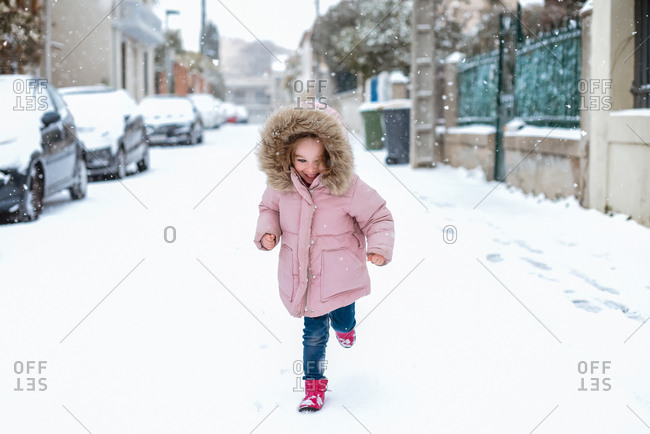 Young girl playing in street in snow in France facing camera