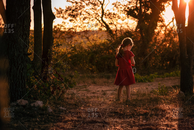 Young girl pensive stands alone in golden light in between trees