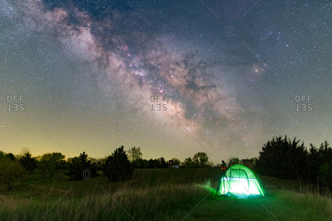 backcountry camping in a lamp-lit tent under stars and the Milky way