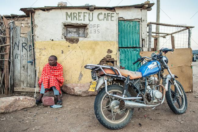 Kenya, Nakuru County - September 18, 2016: Maasai man in front of old cafe sitting with Maasai blanket near bike