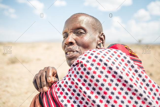 Kenya, Nakuru County - September 18, 2016: Old Maasai woman sitting down in the savannah under the sun smiling