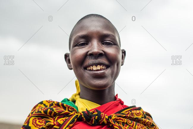 Kenya, Nakuru County - September 21, 2016: Young Maasai woman with short hair and colorful clothes smiling