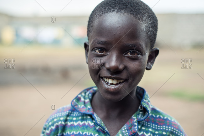Kenya, Nakuru County - September 21, 2016: Kenyan boy with short hair and handsome face smiling to the camera