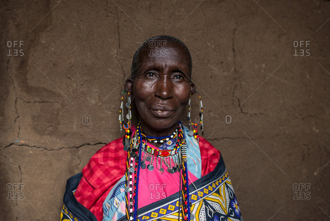 Kenya, Nakuru County - September 22, 2016: Old Maasai woman with jewelry and traditional colorful clothes in hut