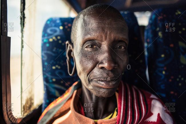Kenya, Nakuru County - September 18, 2016: Old Maasai woman sitting in a public bus smiles next to window seat