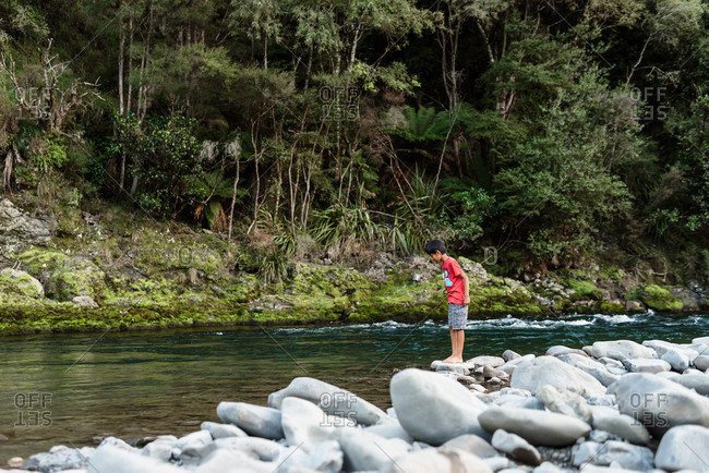 Tween boy looking in water at the edge of a river