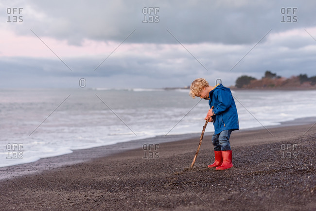 Young boy wearing red boots at beach