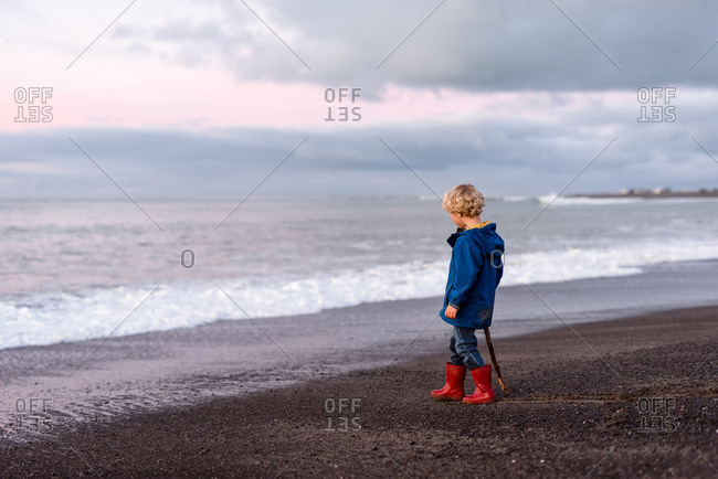 Curly haired preschooler looking at the sea