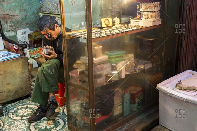 Vietnam, Hanoi - February 25, 2018: A Vietnamese man fixes a watch with an eye-glass in Hanoi, Vietnam.