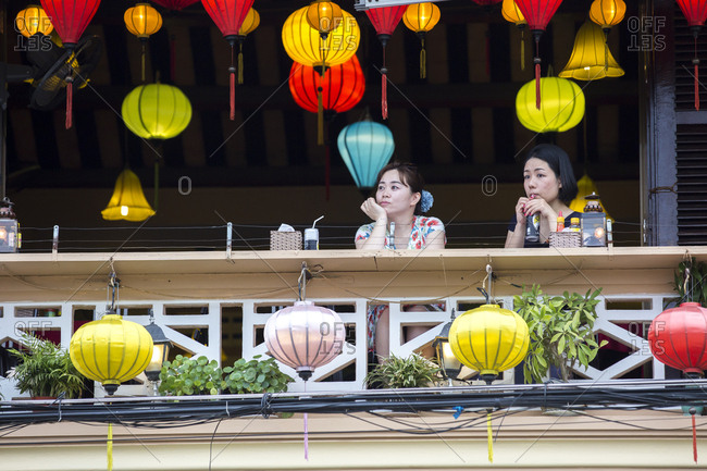 Vietnam, Quang Nam Province, Hoi An - March 3, 2018: Two women enjoy drinks surrounded by lanterns in Hoi An, Vietnam.