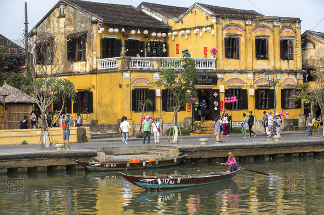 Vietnam, Quang Nam Province, Hoi An - March 3, 2018: Woman on a boat with Hoi An street scene in the background