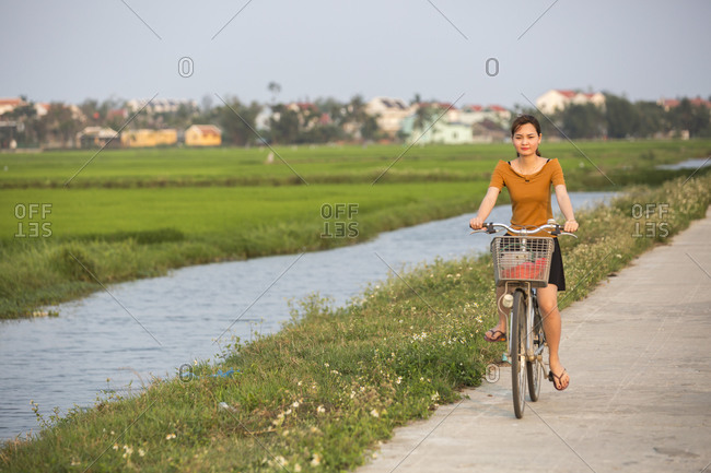 Vietnam, Quang Nam Province, Hoi An - March 4, 2018: A young woman rides a bicycle past a rice paddy in Hoi An, Vietnam.